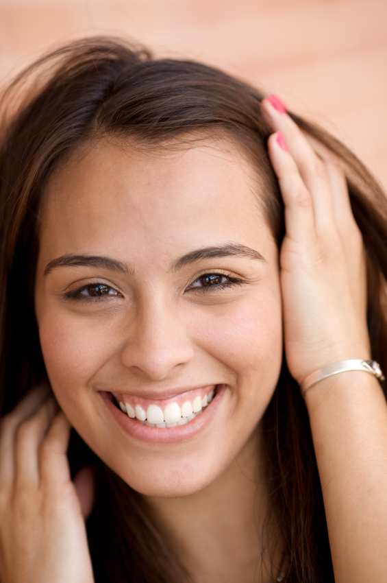 Beautiful hispanic woman smiling with hand in hair