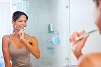 woman looking at mirror brushing teeth  tooth  bathroom  eNewsletter